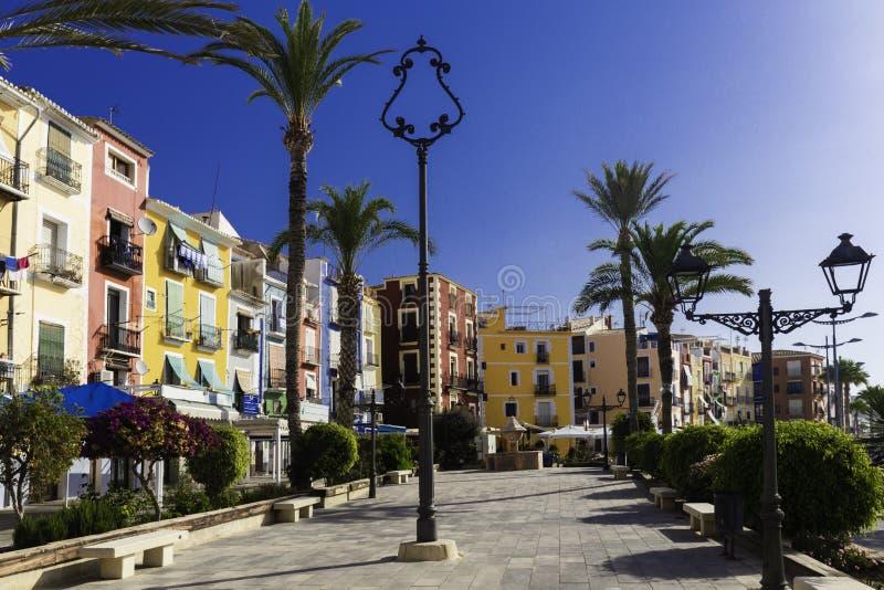 Passeio bonito com flores, palmeiras, árvores contra as casas coloridas da cidade antiga da Espanha de Villajoyosa imagens de stock