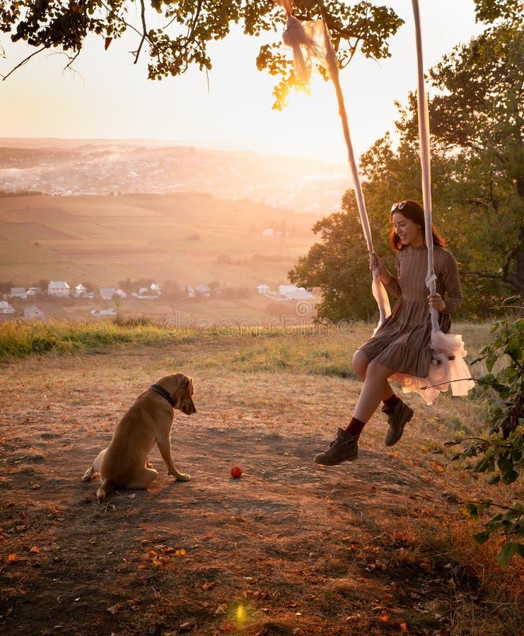 Passeio bonito e feliz da menina em um balanço na perspectiva da cidade ao lado de um cão de assento fotografia de stock