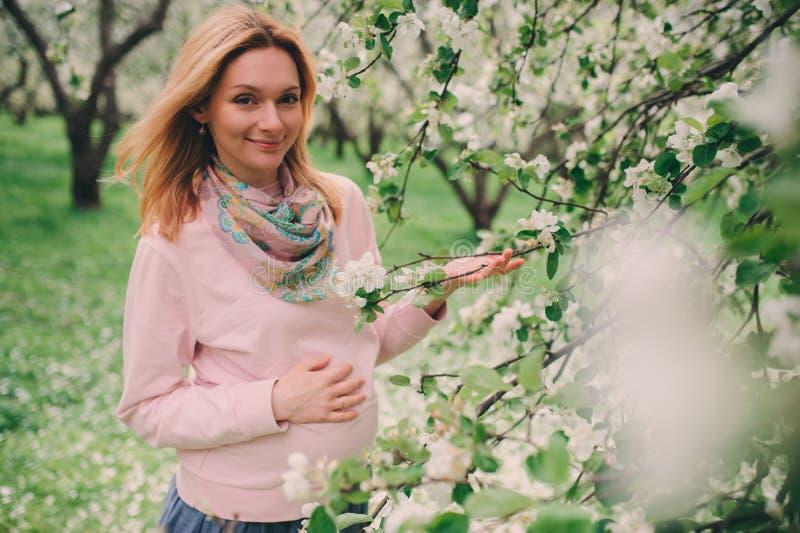 Passeio bonito louro grávido feliz da mulher exterior no parque ou no jardim da mola fotos de stock