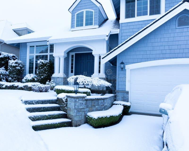 Passeio coberto de neve na frente da casa durante a queda de neve do inverno imagens de stock