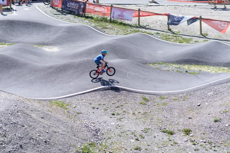 Passeio da criança uma bomba da bicicleta no CAMPEONATO DO MUNDO 2019 de MERCEDES-BENZ UCI MTB - DHI Vallnord, Andorra em julho d imagem de stock