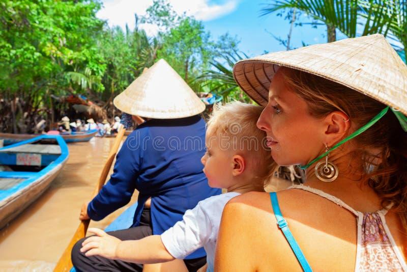 Passeio da família no barco vietnamiano tradicional no delta de Mekong River foto de stock