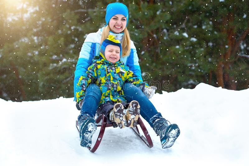 Passeio da mãe e do filho no trenó Brincadeira no divertimento exterior do inverno da floresta nevado para férias do Natal da fam imagem de stock