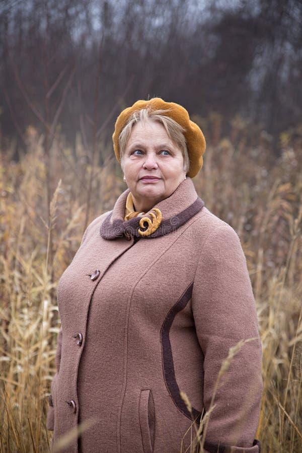 Passeio da mulher do pensionista exterior no outono imagem de stock royalty free