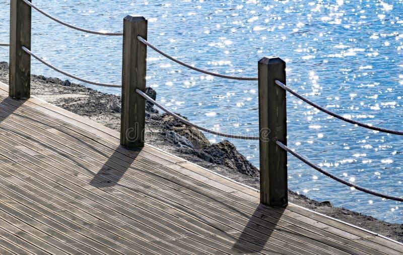 Passeio de madeira ao longo da costa com uma cerca com uma corda Paisagem do ver?o do mar fotos de stock royalty free
