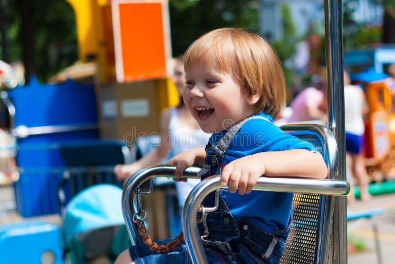 Passeio de montada de sorriso do divertimento do menino justo da criança fotografia de stock royalty free