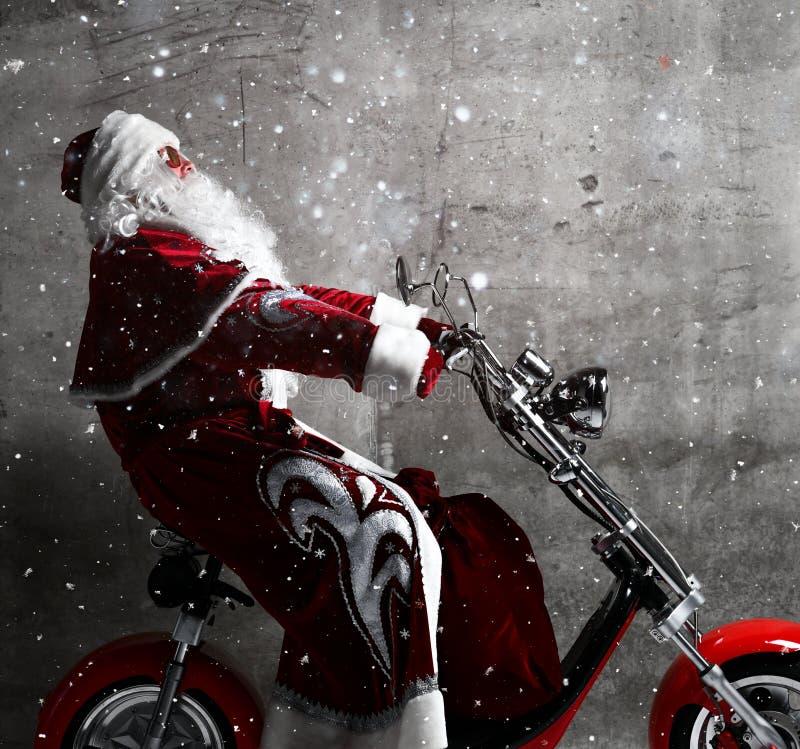Passeio de Santa Claus uma motocicleta nova do velomotor sob a neve Ano novo e Feliz Natal fotografia de stock