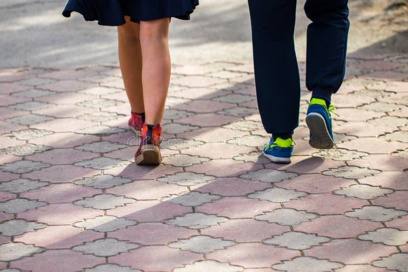 Passeio em sapatas do esporte no pavimento no dia de mola fotografia de stock royalty free