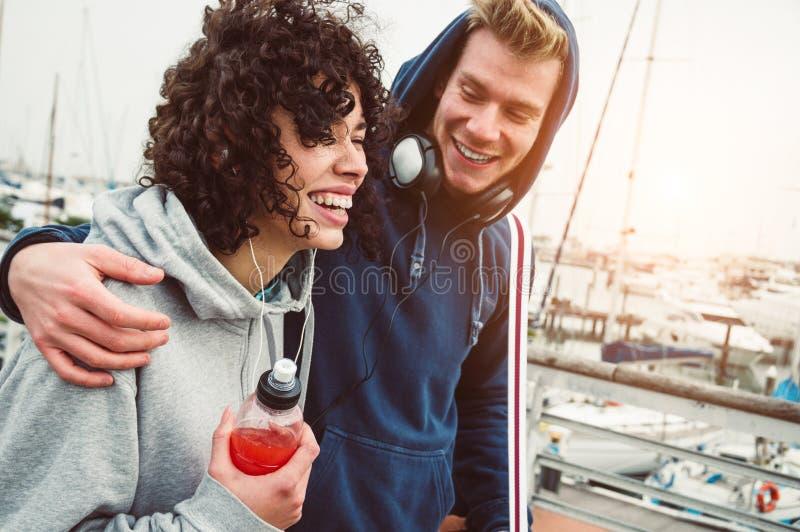 Passeio exterior de sorriso dos pares novos ocasionais no porto fotografia de stock royalty free