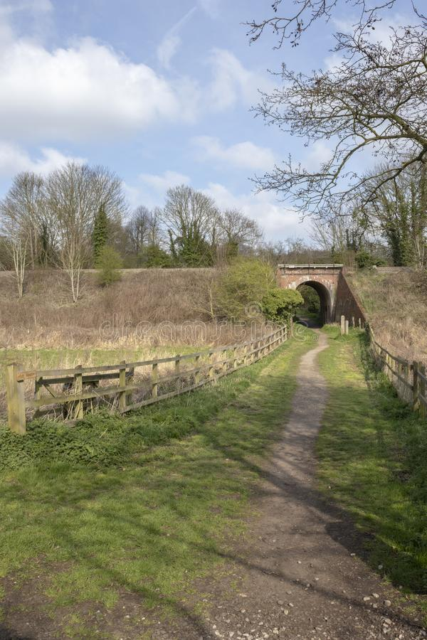 Passeio que vai sob a ponte de estrada de ferro, verde do mil?nio de Halesworth, Suffolk, Inglaterra fotos de stock royalty free