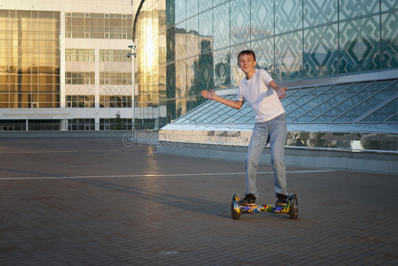 Passeios adolescentes um gyroscooter, com um sorriso e umas emoções positivas fotos de stock