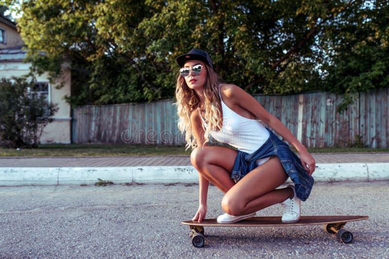Passeios bronzeados da mulher, os elegantes e os à moda da menina na maneira ao skate, longboard Roupa de banho branco do bodysui fotografia de stock royalty free