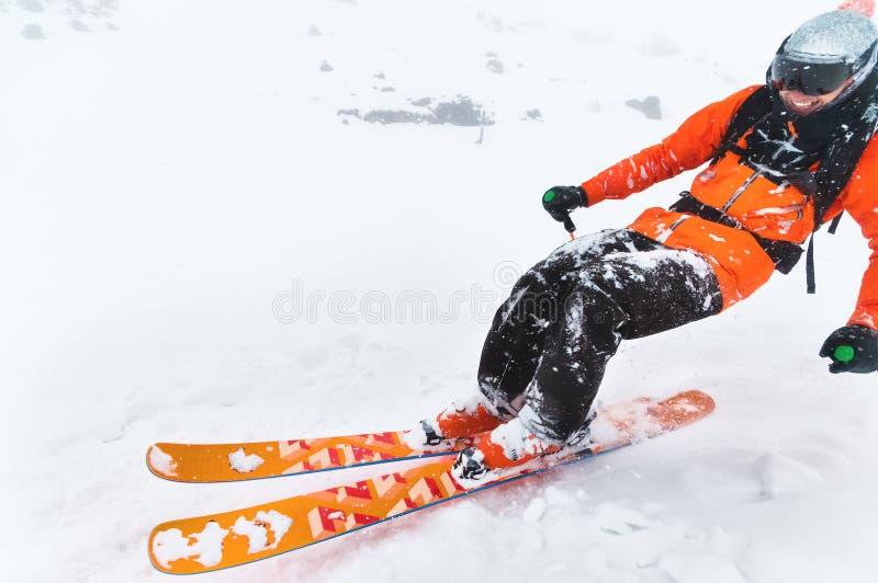 Passeios de riso profissionais do atleta do esquiador do close-up fora da neve profunda ao executar um truque de esqui em uma tem fotos de stock royalty free