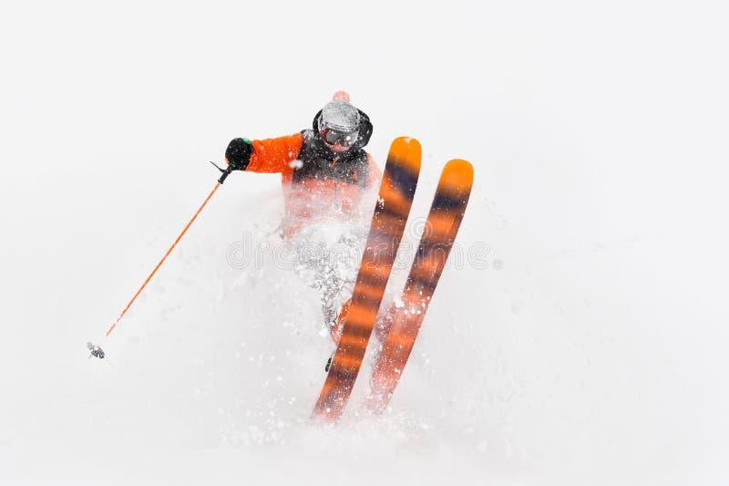 Passeios profissionais do atleta do esquiador fora da neve profunda ao executar um truque de esqui em uma tempestade de neve A es imagens de stock
