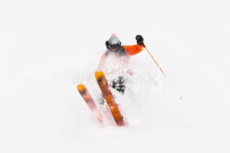 Passeios profissionais do atleta do esquiador fora da neve profunda ao executar um truque de esqui em uma tempestade de neve A es imagem de stock royalty free
