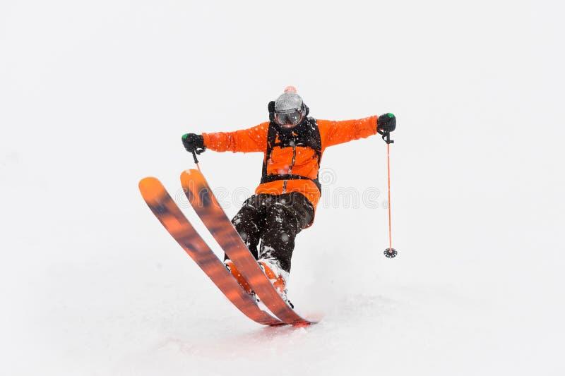 Passeios profissionais do atleta do esquiador fora da neve profunda ao executar um truque de esqui em uma tempestade de neve A es fotografia de stock royalty free
