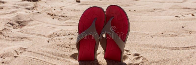 Passen Sie Flipflops im Sand eines Strandes zusammen lizenzfreie stockbilder