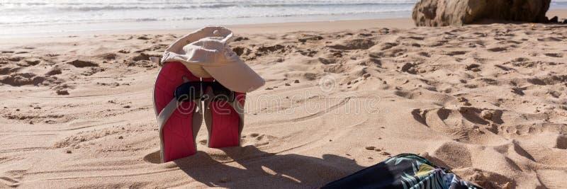 Passen Sie Flipflops mit Sonnenbrille im Sand des Strandes zusammen stockfotos