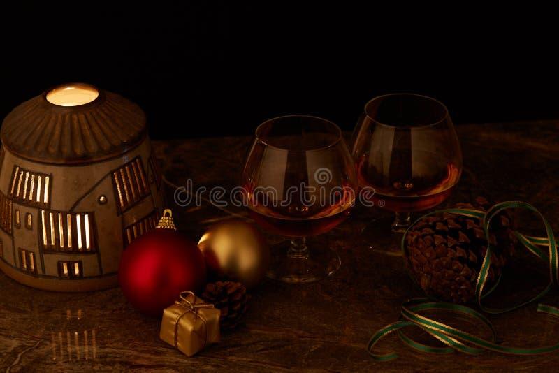 Passen Sie von den Gläsern Alkohol auf verzierter Weihnachtstabelle mit Kerzenlampe und schwarzem Hintergrund zusammen stockbilder