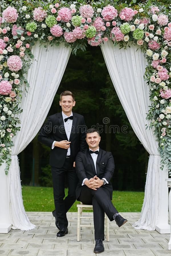 Passen Sie von den hübschen jungen Männern in den weißen Hemden und in den stilvollen schwarzen Anzügen mit Fliege zusammen und u stockfoto