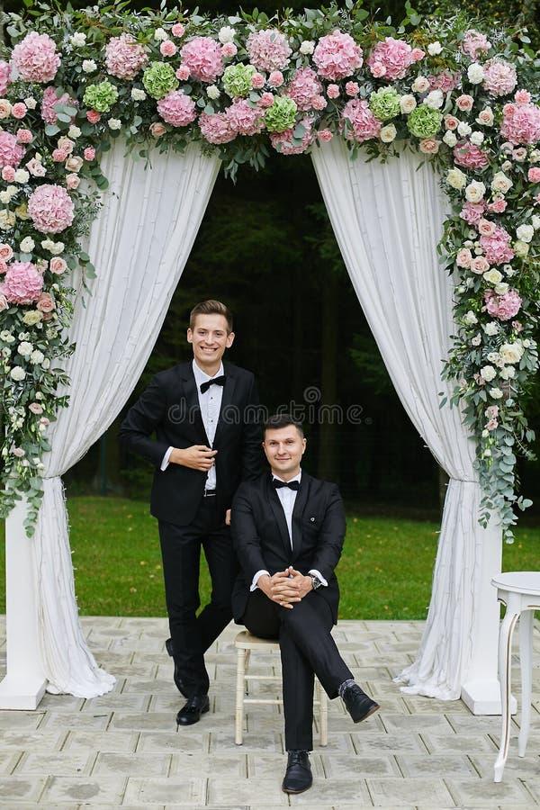 Passen Sie von den modernen und hübschen jungen Männern im weißen Hemd und im stilvollen schwarzen Anzug mit Fliege zusammen und  stockbild