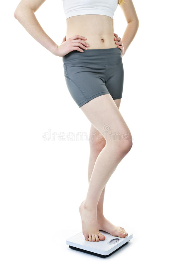 Passende Frau, die auf Badezimmerskala steht stockbilder