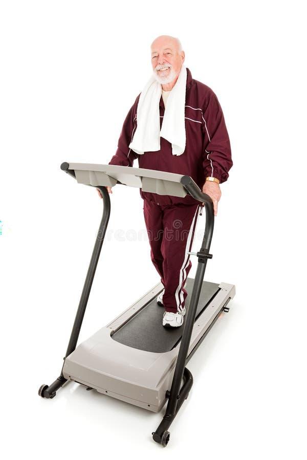 Passender älterer Mann auf Tretmühle stockbilder