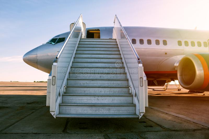 Passenger aircraft with a boarding ramp on the airport apron stock image