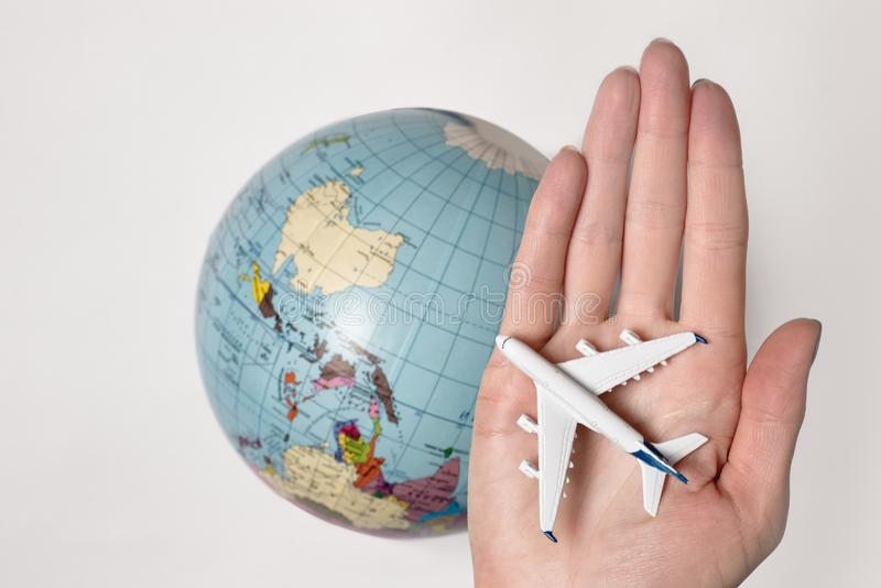 Passenger aircraft on the female palm on the background of the globe. Concept of air travel on a light background.  royalty free stock photo