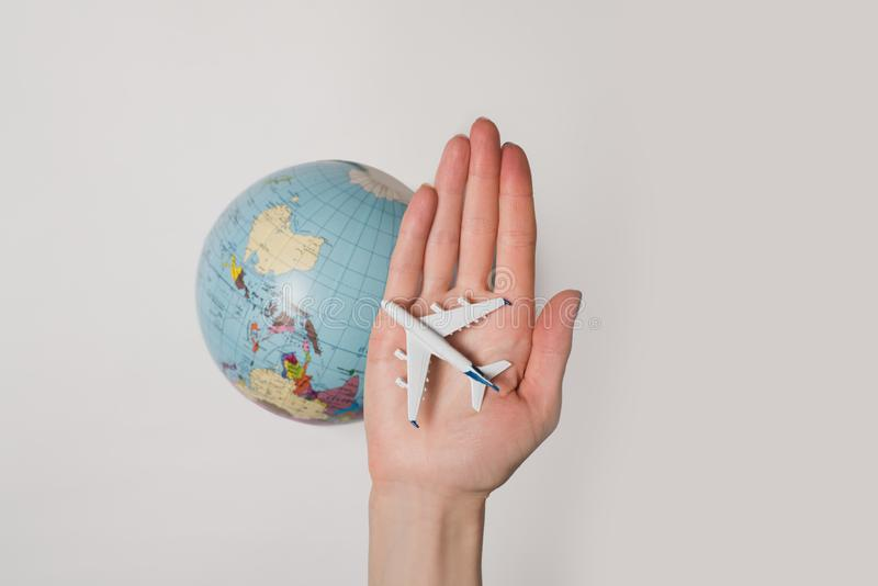 Passenger aircraft on the female palm on the background of the globe. Concept of air travel on a light background.  royalty free stock photos