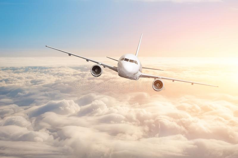 Passenger aircraft flying above the clouds horizon sky with bright sunset colors.  stock photography