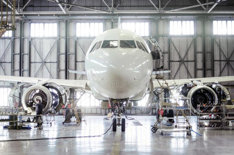 Passenger aircraft on maintenance of engine and fuselage repair in airport hangar. Passenger aircraft on maintenance of engine and fuselage repair in airport stock photo