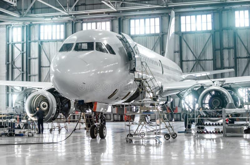 Passenger aircraft on maintenance of engine and fuselage repair in airport hangar. Passenger aircraft on maintenance of engine and fuselage repair in airport stock image