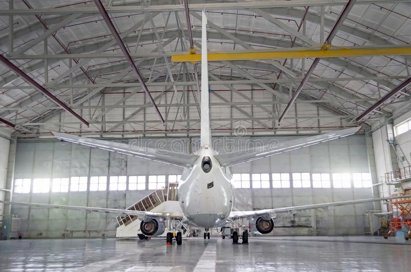 Passenger aircraft on maintenance of engine and fuselage repair in airport hangar. Rear view of the tail. Passenger aircraft on maintenance of engine and royalty free stock images