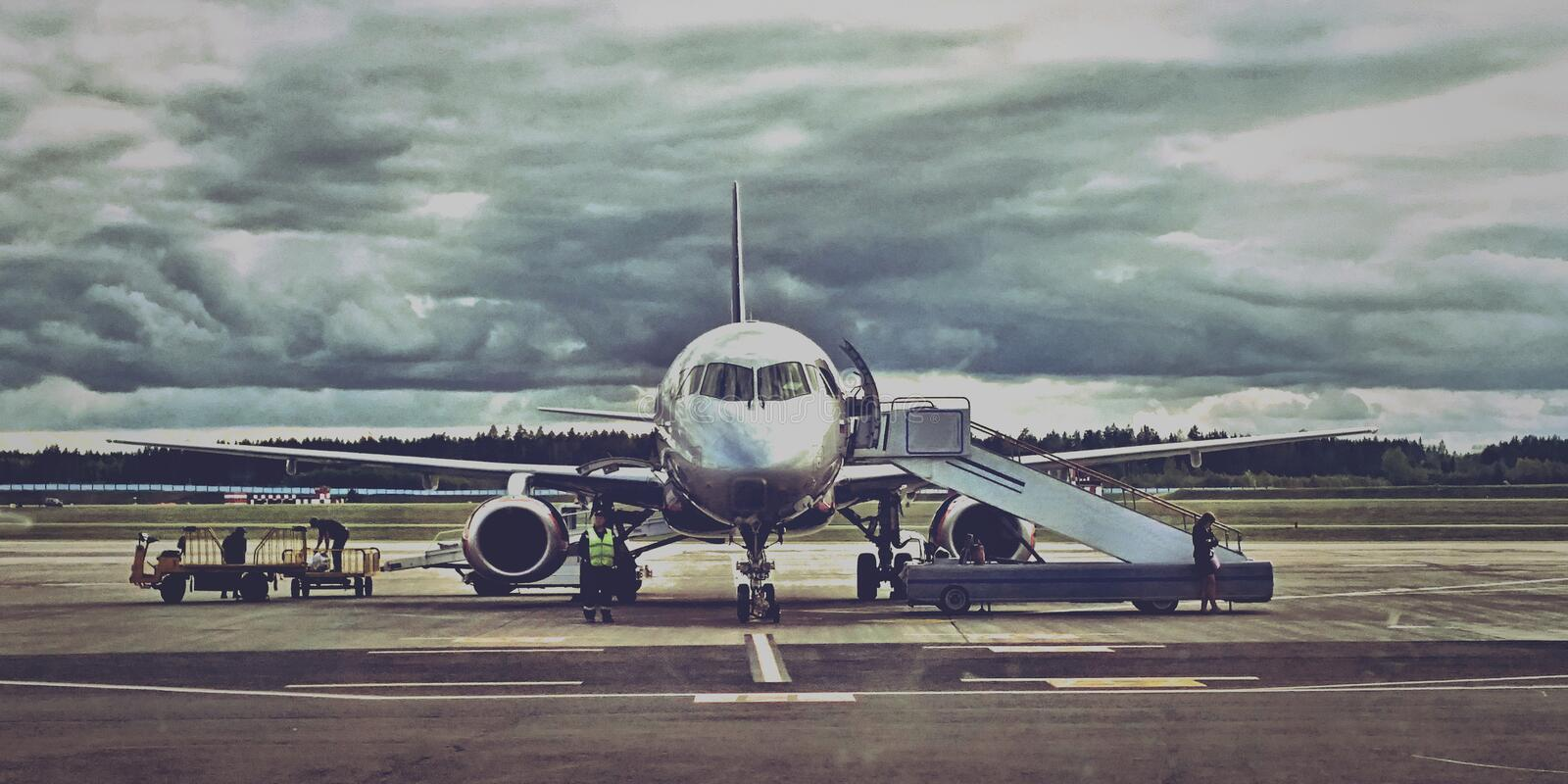 Passenger aircraft near the ladder. Civil aviation aircraft in the parking lot on a cloudy day royalty free stock images