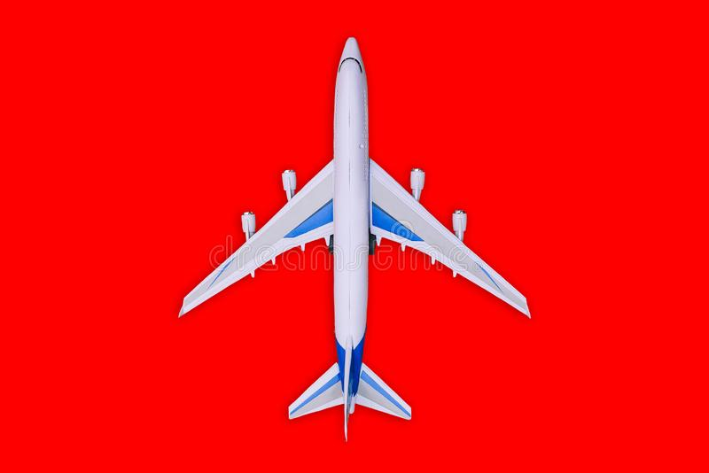 Passenger aircraft on a red background. Summer holidays and air travel concept. Tourism and travel background. Buying or. Booking online tickets royalty free stock photography