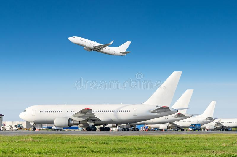 Passenger aircraft row, airplane parked on service before departure at the airport, other plane push back tow. One take off from t stock photo