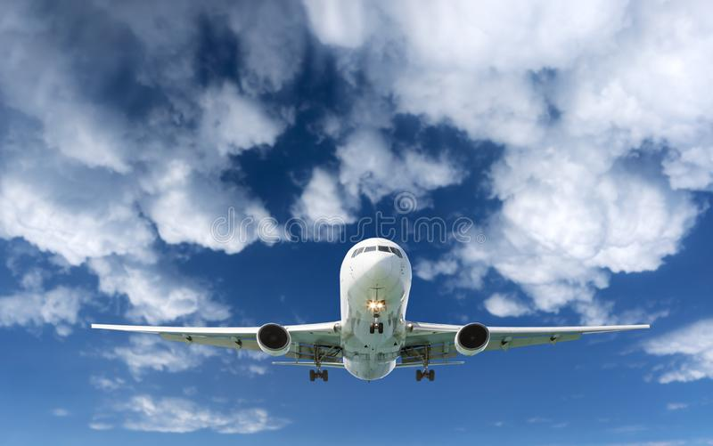 Passenger Airliner Airplane flying in the sky white clouds royalty free stock images
