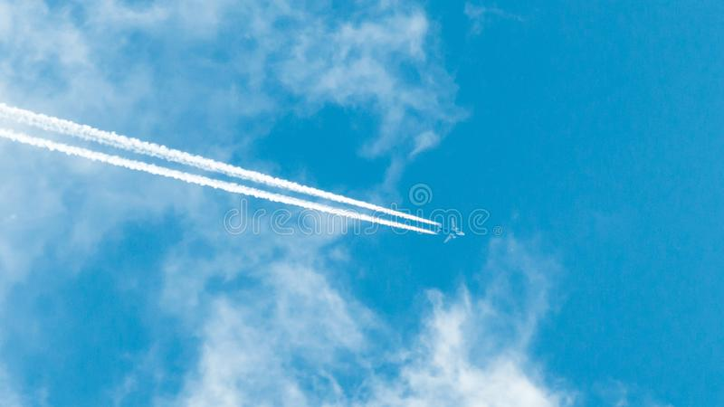 Passenger airliner flies out of the cloud. two traces of the working aircraft engines. Clear blue sky and clouds. travelling by plane. air flight royalty free stock photography