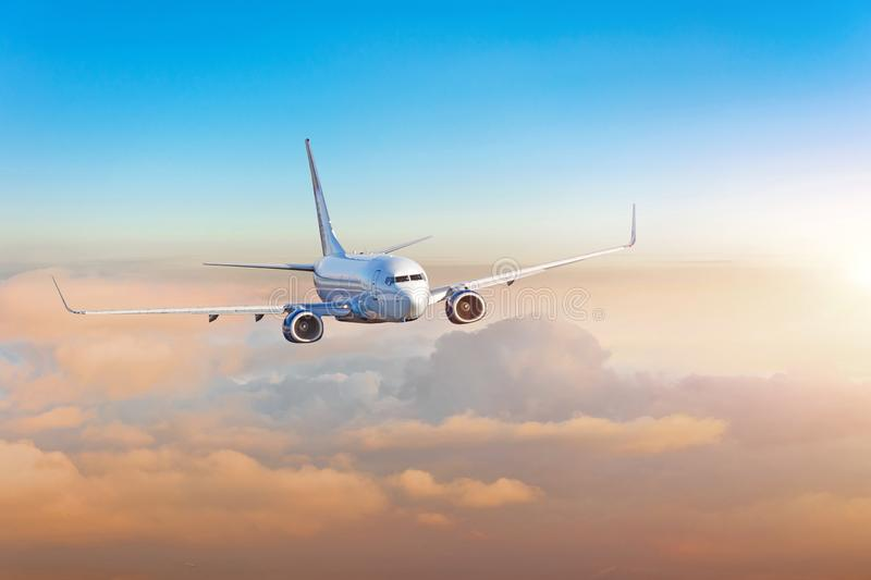 Passenger airplane, business trip, travel concept. Flying evening colorful sunset royalty free stock image