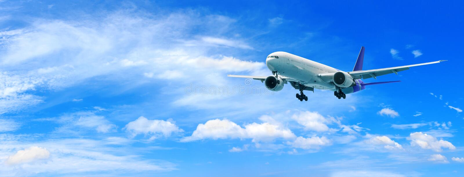 Passenger airplane flying above clouds. View from the window plane to amazing sky with beautiful clouds. stock photography