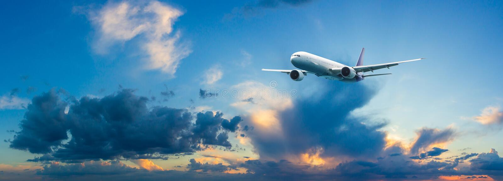 Passenger airplane flying above night clouds and amazing sky at the sunset. stock photo