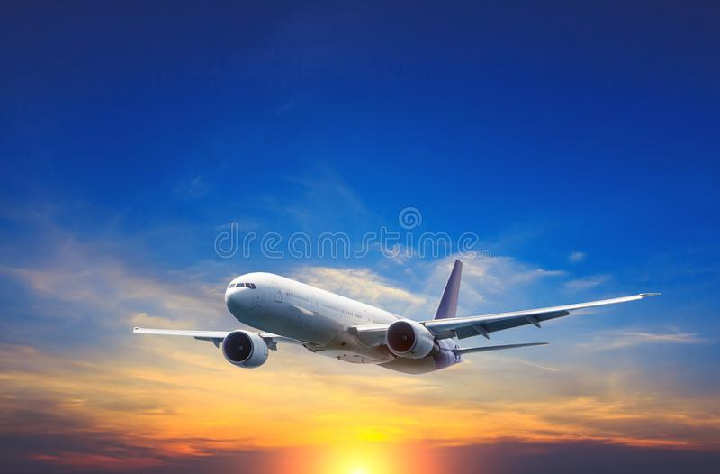 Passenger airplane flying above night clouds and amazing sky at the sunset. royalty free stock image