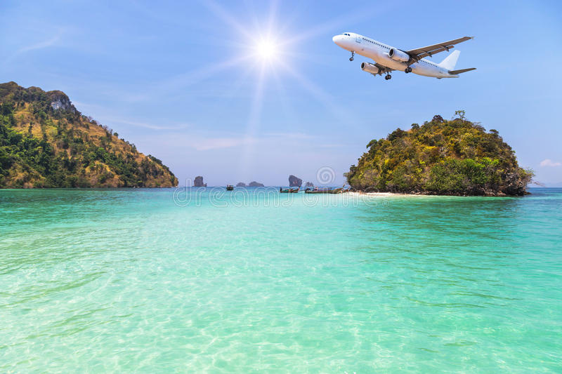 Passenger airplane flying above small limestone island in tropical andaman sea stock image