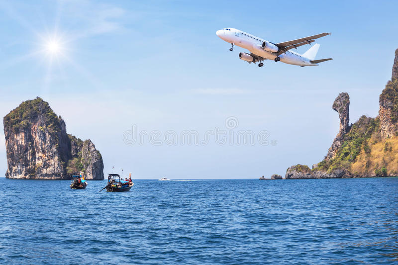 Passenger airplane flying above small limestone island in tropical andaman sea with sunlight. stock images
