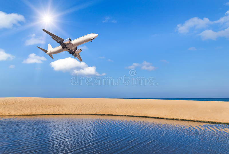 passenger airplane flying above tropical beach in andaman sea on blue sky with sunlight stock photo