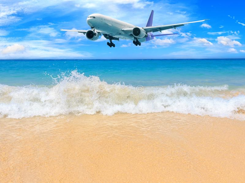 Passenger airplane flying above tropical beach in Phuket, Thailand. Amazing view of blue sea and golden sand. royalty free stock images