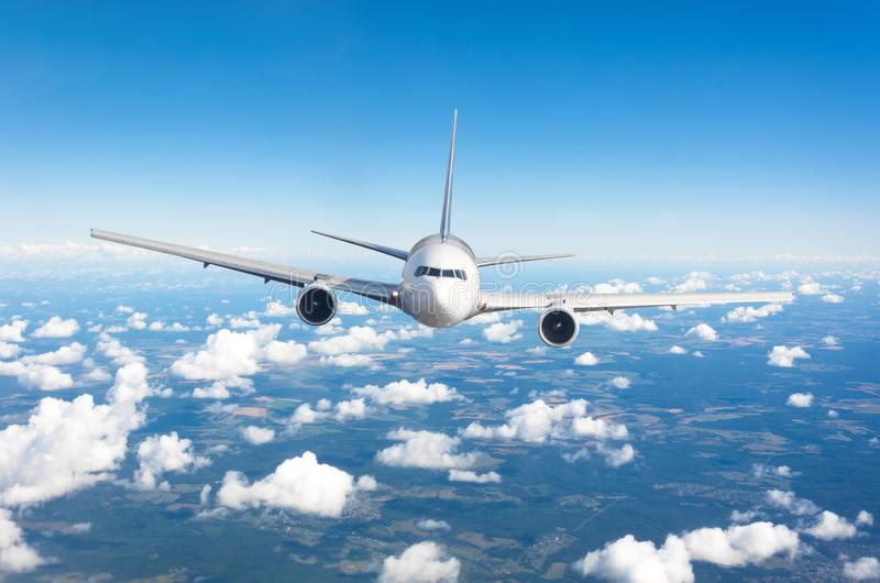Passenger airplane flying at flight level high in the sky above cumulus clouds and blue sky. View directly in front, exactly. stock images