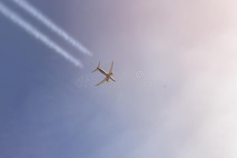 Passenger airplane flying high in clear sky leaving white trails. Big plane flying during sunset time with dramatic sky on backgro royalty free stock image