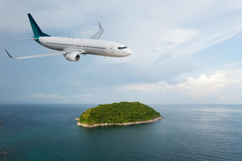 Passenger airplane flying over above island tropical sea in stock photography